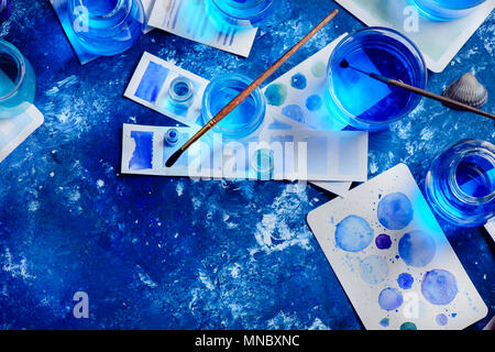 Creative artist workplace with marine watercolor, palettes, swatches, brushes and water jars from above. Painting sea concept on a navy blue backgroun - Stock Photo