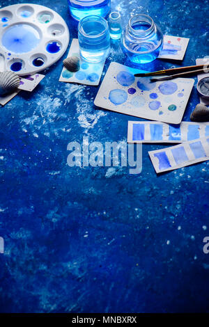 Artist workplace with watercolor sketches in shades of blue. Monochromatic painting with glass jars, paint and brushes. Drawing sea concept with copy  - Stock Photo
