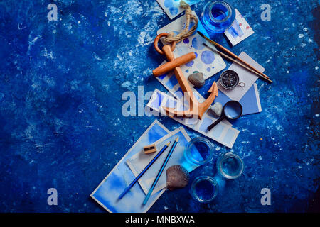 Artist workplace with watercolor sketches, seashells, wooden anchor and compass on a navy blue background with copy space. Creative travel and paintin - Stock Photo