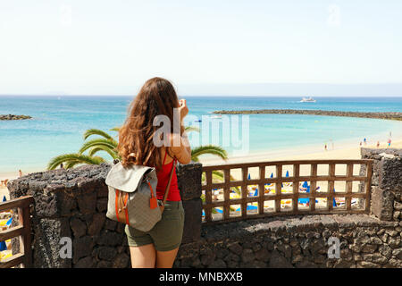 Back view of traveler girl taking picture of Playa Dorada seascape, Lanzarote, Canary Islands - Stock Photo