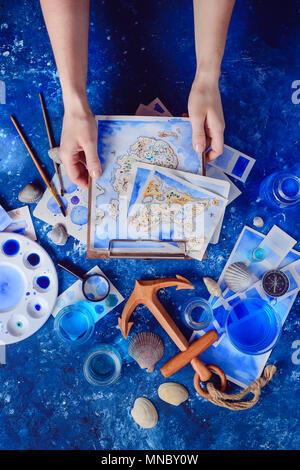 Hands holding a hand-painted map on a clipboard. Marine watercolor concept. Creative artist workplace flat lay. - Stock Photo