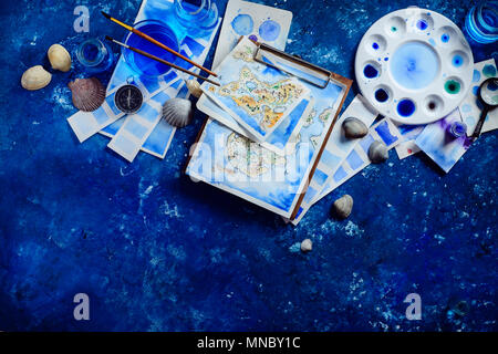 Handpainted fantasy map on a navy blue background with copy space. Artist workplace with watercolor sketches. Creative travel concept. - Stock Photo