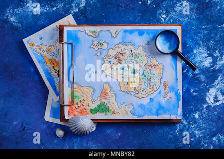 Sea travel and painting concept. Watercolor fantasy map on a wooden clipboard with a magnifying glass on a navy blue background with copy space. - Stock Photo