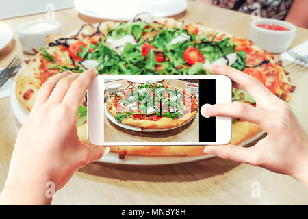 Composite image of making pizza photos on a smartphone - woman's hands holding mobile phone and touching shutter button on the screen. - Stock Photo