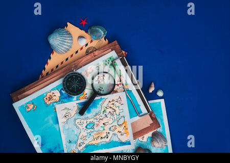 Header with sea travel and exploration concept. Watercolor maps on a wooden clipboard, compass and magnifying glass flat lay on a marine blue backgrou - Stock Photo