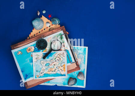 Sea travel and exploration concept. Watercolor maps on a wooden clipboard, compass and magnifying glass flat lay on a navy blue background with copy s - Stock Photo