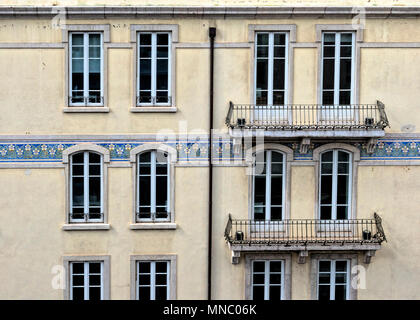Section of an office block showing varied window design, balconies and decorative tiling - Stock Photo