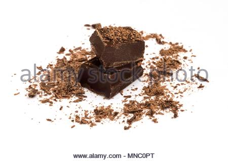 piece of dark chocolate with shavings on white background - Stock Photo