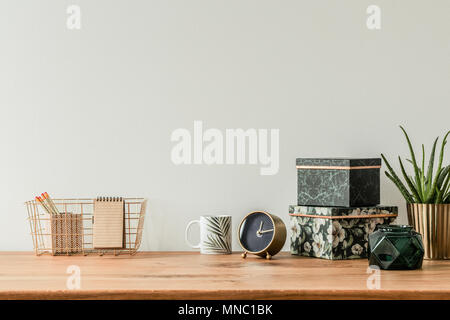 Organized table top with floral boxes, mug, clock and metal box on an empty wall - Stock Photo