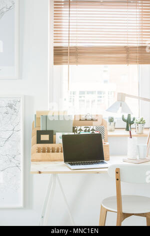 White chair at desk with laptop and wooden organizer in natural home office interior with window - Stock Photo