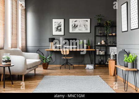 Real photo of open space apartment interior with beige sofa next to the window and desktop computer o a wooden desk - Stock Photo