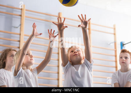 Young girl with her arms up jumping to hit a volleyball during a game with her school team mates at extracurricular physical education class in the gy - Stock Photo