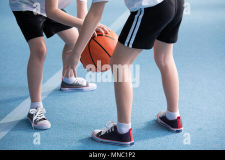 Close-up on young children wearing school sportswear learning to dribble a basketball during physical education classes in gym with blue floor - Stock Photo