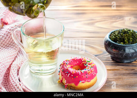 Cup of hot green tea beverages with donut glazed - Stock Photo