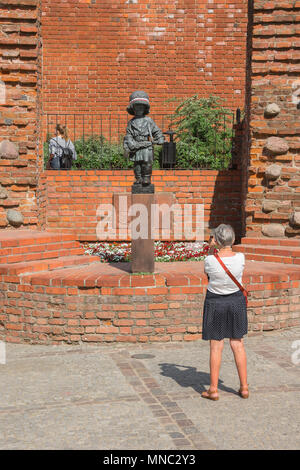 Warsaw Little Insurgent, a woman takes a photo of the Little Insurgent monument commemorating the part played by children in the Warsaw Rising of 1944. - Stock Photo