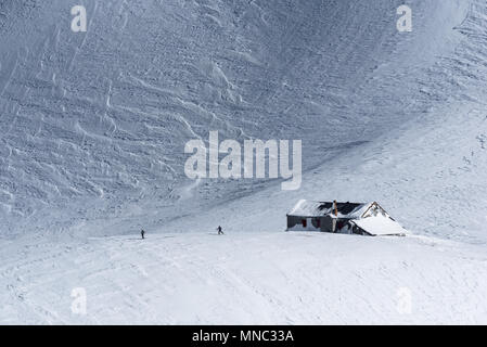 Two skiers leaving mountain hut partly covered by snow against backdrop of huge slope in winter sunshine - Stock Photo