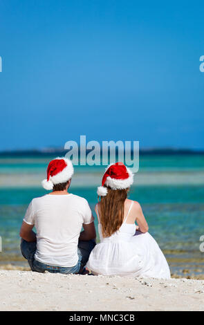 Romantic couple in Santa hats sitting on a tropical beach - Stock Photo