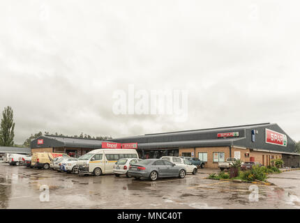 MOOI RIVER, SOUTH AFRICA - MARCH 22, 2018: A supermarket, with many vehicles in front, in Mooi River, in the Kwazulu-Natal Midlands. Falling rain is v - Stock Photo