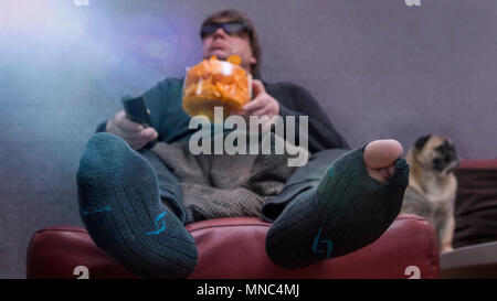 A man eats chips in front of the TV. His dog is sitting next to him on the couch. The man has a hole in the stockings and a 3 D glasses put on. Frog p