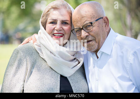 Closeup portrait, retired couple in white shirt and dress holding each other smiling,enjoying life together, isolated outside green trees background. - Stock Photo