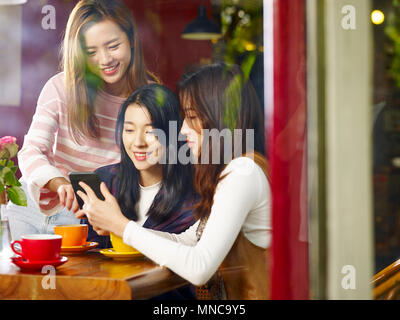 three happy beautiful young asian women sitting at table chatting talking playing with cellphone in coffee shop or tea house, shot through window glas - Stock Photo