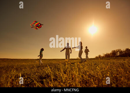 Happy family with a kite playing at sunset in the field - Stock Photo