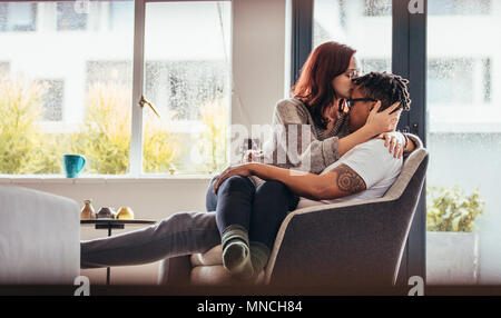 Woman kissing boyfriend forehead with love while sitting on a chair together. Romantic interracial couple at home. - Stock Photo
