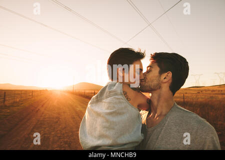 Couple kissing on a mud track highway in countryside. Romantic couple on the highway spending time together. - Stock Photo
