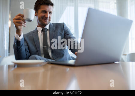 Happy young businessman using laptop and having coffee at office. Male executive working on laptop during coffee break. - Stock Photo