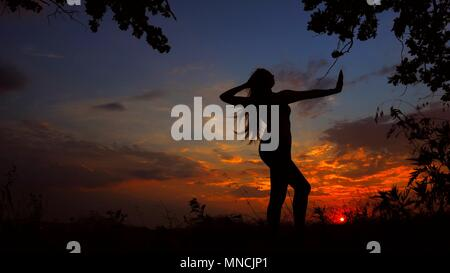 Black female silhouette meditating in evening and doing yoga in sunset background. - Stock Photo