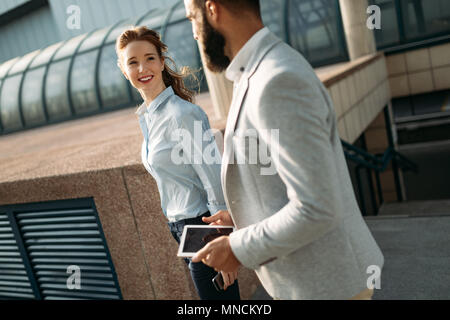 Business partners workmate couple talking in an urban city - Stock Photo
