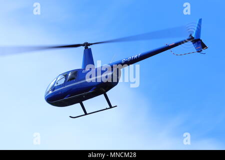 A Robinson R44 helicopter G-OTRT flying over Leeds Bradford International Airport - Stock Photo