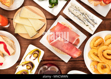 The food of Spain. An overhead photo of different Spanish tapas, shot from above on a dark rustic texture. Jamon, cheese, gildas, anchovies, calamari  - Stock Photo