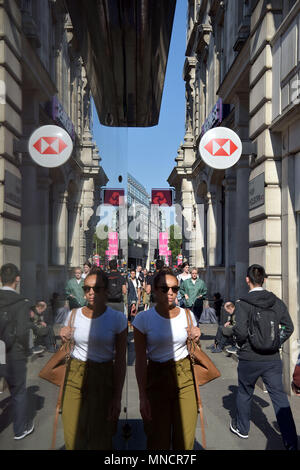 People walk past the bank branches of the HSBC and NatWest banks on High Holborn, central London. - Stock Photo