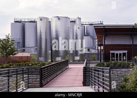 Huge metal malt silos shine in the sun at the New Belgium Brewery in Asheville, NC, USA - Stock Photo