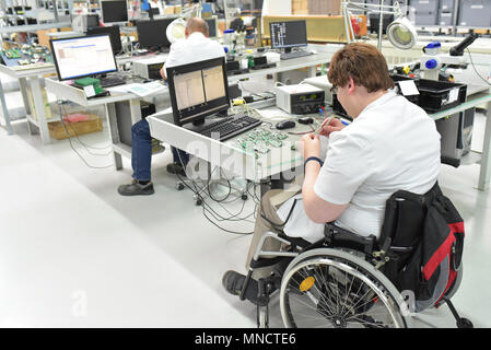 handicapped worker in a wheelchair assembling electronic components in a modern factory at the workplace - Stock Photo