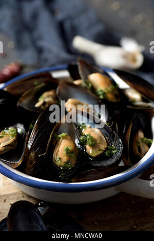 closeup of a ceramic bowl with moules mariniere, a french recipe of mussels, on a rustic wooden table - Stock Photo