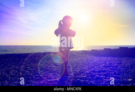 LONDON, ENGLAND - FEBRUARY 17 : Young child in silhouette walking along a shingle beach as the sun goes down. Bexhill and De La Warr Pavilion Bexhill-on-Sea, East Sussex. 29 November 2015. United Kingdom. - Stock Photo