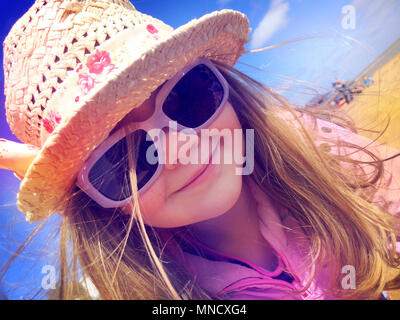 LONDON, ENGLAND - APRIL 15 : A young girl with a big smile, sunglasses in a straw hat on a beach in Broadstairs on April 15, 2014, United Kingdom. - Stock Photo