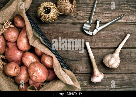 Raw whole washed organic potatoes and garlic on sackcloth over old wooden plank background. Top view with space. Close up. Still life. Copy space. Fla - Stock Photo