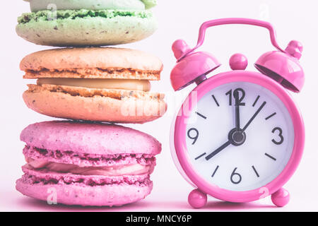 Colorful macaroons and small alarm clock on pastel pink background minimal creative concept. - Stock Photo