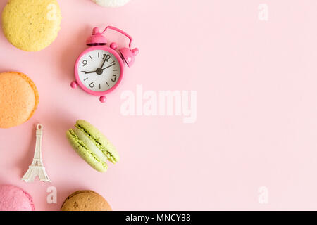 Flat lay of colorful macaroons, small alarm clock and Eiffel Tower French food and culture minimal concept. Space for copy. - Stock Photo