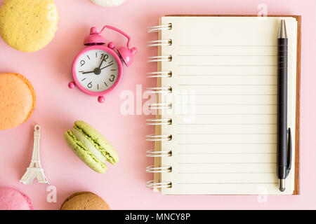 Flat lay of colorful macaroons, small alarm clock, Eiffel Tower and clean notebook against pastel pink background. - Stock Photo
