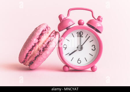Close up of macaroon and small alarm clock model on pink background. - Stock Photo