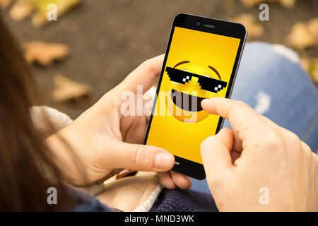 communications concept: woman holding a 3d generated smartphone with meme on the screen. Graphics on screen are made up. - Stock Photo