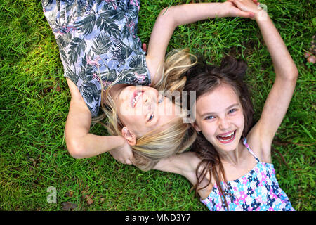 joyful friends lie on the grass and laugh - Stock Photo