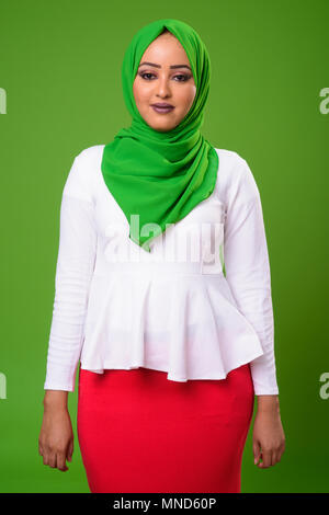 Young African Muslim woman against chroma key with green background - Stock Photo