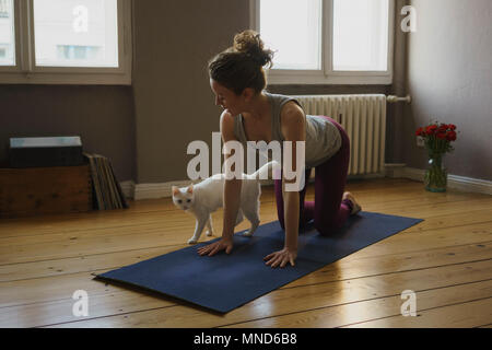 Full length of woman practicing cow pose on exercise mat by cat at home - Stock Photo