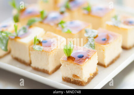 Appetizing cheesecake with mint leaves. Delicious sliced dessert on white plate. - Stock Photo