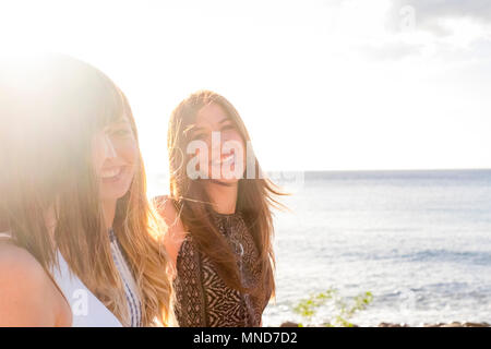 Three young women friends walk together on a wall near the beach in Tenerife. Enjoy the vacation under a blue sky with yellow sun. Hands by hands. - Stock Photo